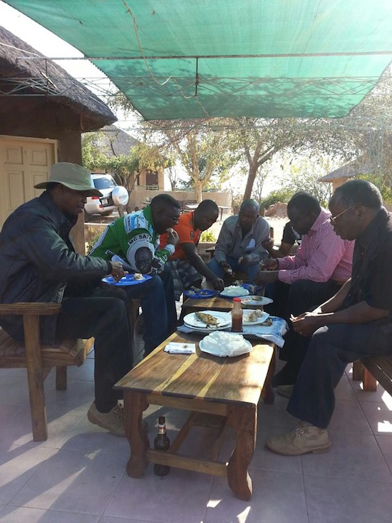 Lungu eating nshima with bottle of beer under the table