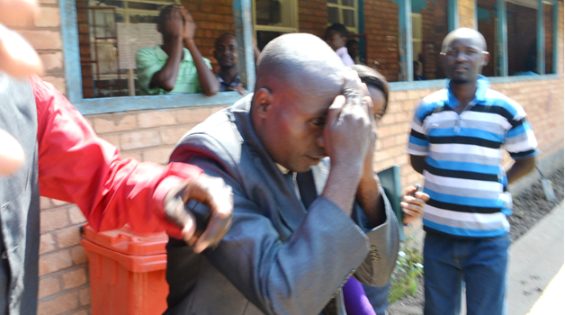 Bishop Nyondo hiding his face in shame at court