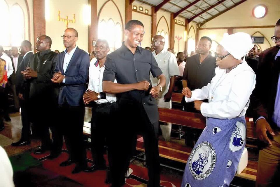 Lungu and Mumbi dancing in church while every is praying