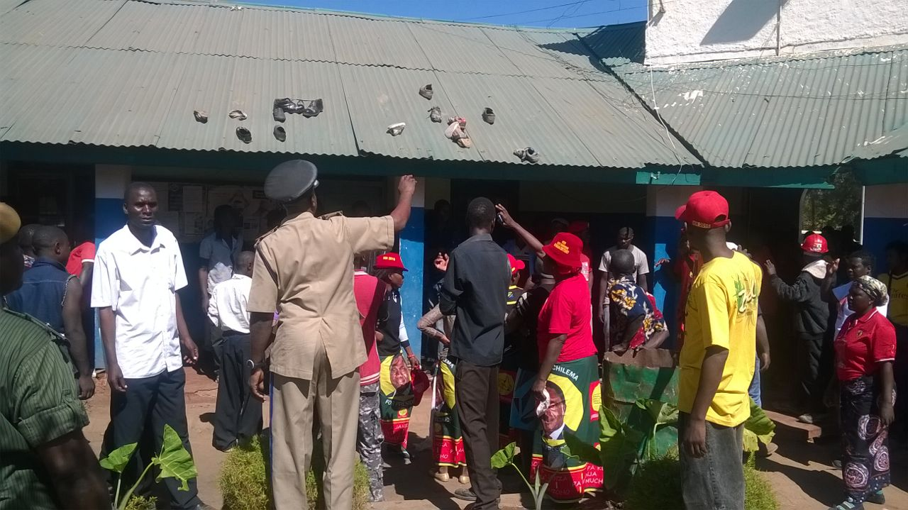 UPND cadres exchange words with police officers, above: Chibwana (white) hat shortly after his arrest
